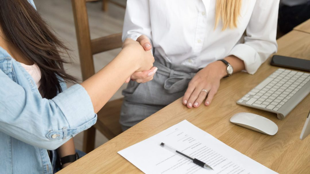 Two women partners handshaking after signing business contract at meeting, female client or customer and manager agent broker closing good deal, female hands shaking making agreement, close up view